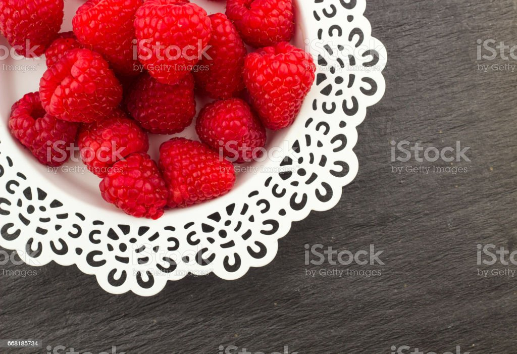 Fresh Red Raspberries on a white artistic plate / Red Fresh Raspberries on a white artistic plate with cookies, rosemary, chocolate and cream in the background. stock photo