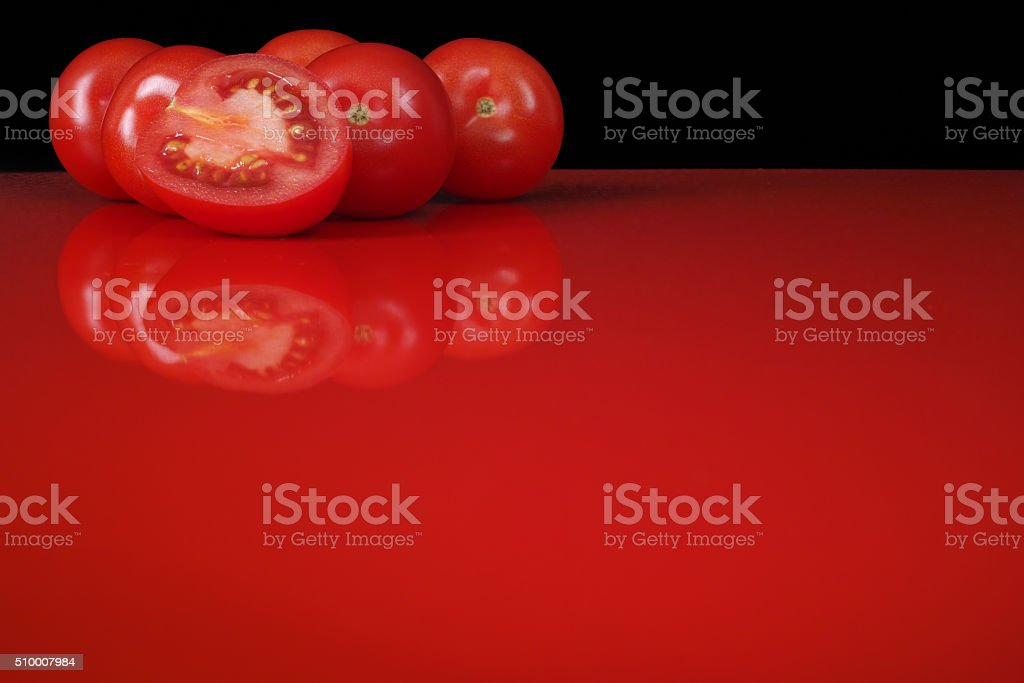 Fresh red Roma tomatoes on red table, refletion, copy space stock photo