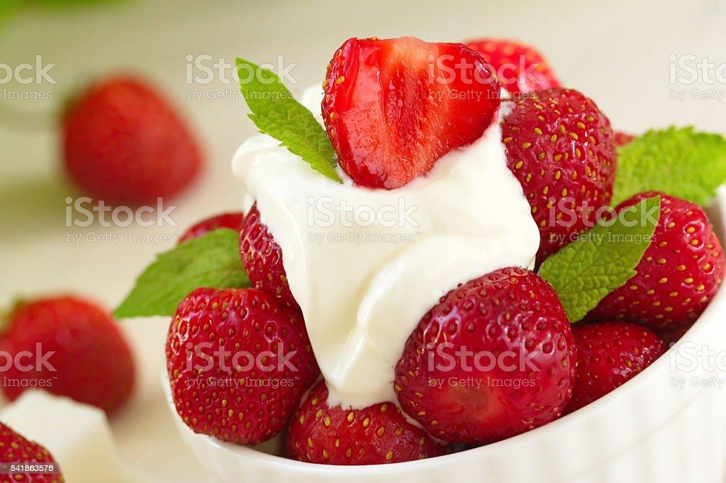 Fresh red strawberries with cream stock photo