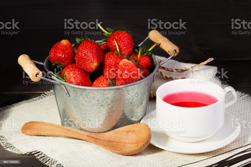fresh red strawberry in bucket on black wooden table with black color background. stock photo