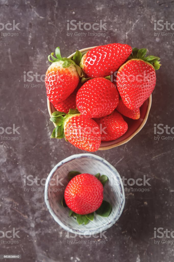 Fresh red strawberry with green leaves. Dark background. Ingredients for smoothies. stock photo