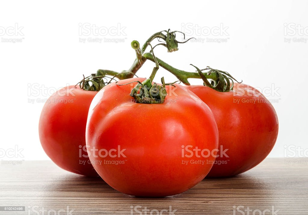 Fresh red tomatoes on a wooden kitchen table stock photo