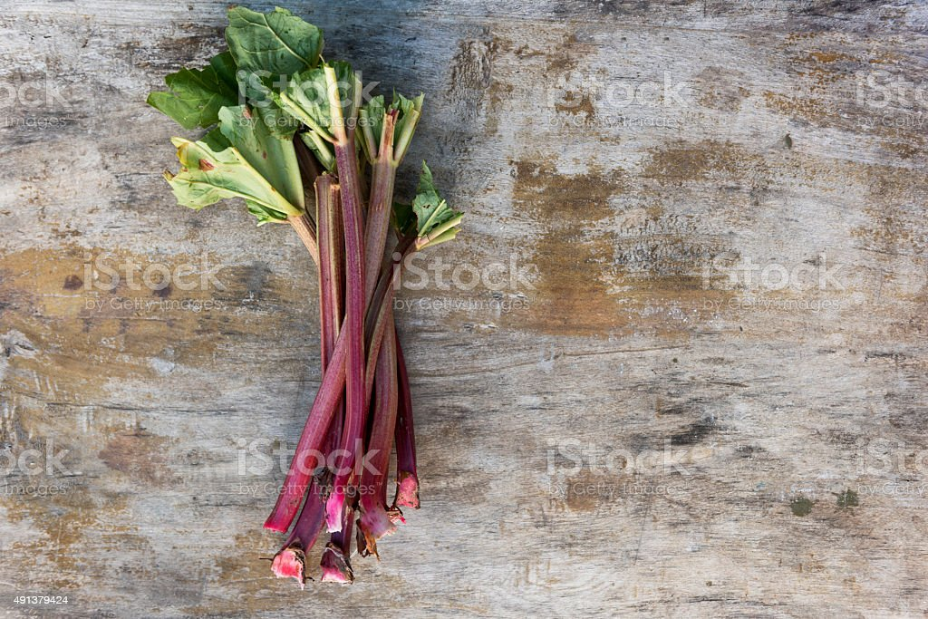 Fresh Rhubarb Stalks Against a Weathered Wooden Background stock photo