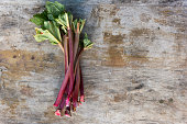 Fresh Rhubarb Stalks Against a Weathered Wooden Background