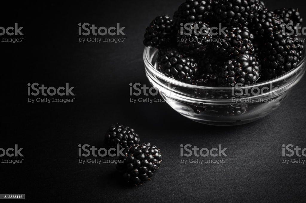 Fresh Ripe Juicy Blackberries in a plate on black background stock photo
