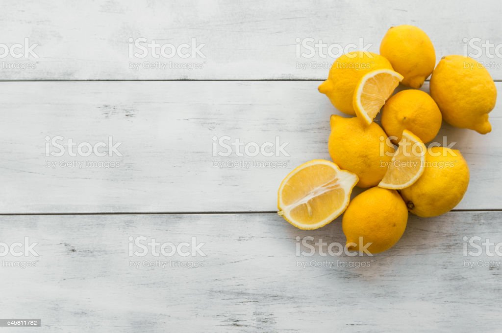 fresh ripe lemons on white wooden table stock photo