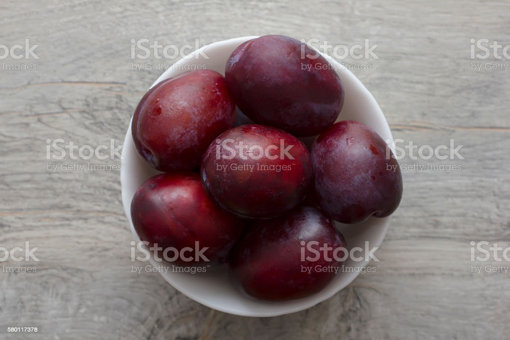 Fresh, ripe plums in white bowl on wooden texture table stock photo