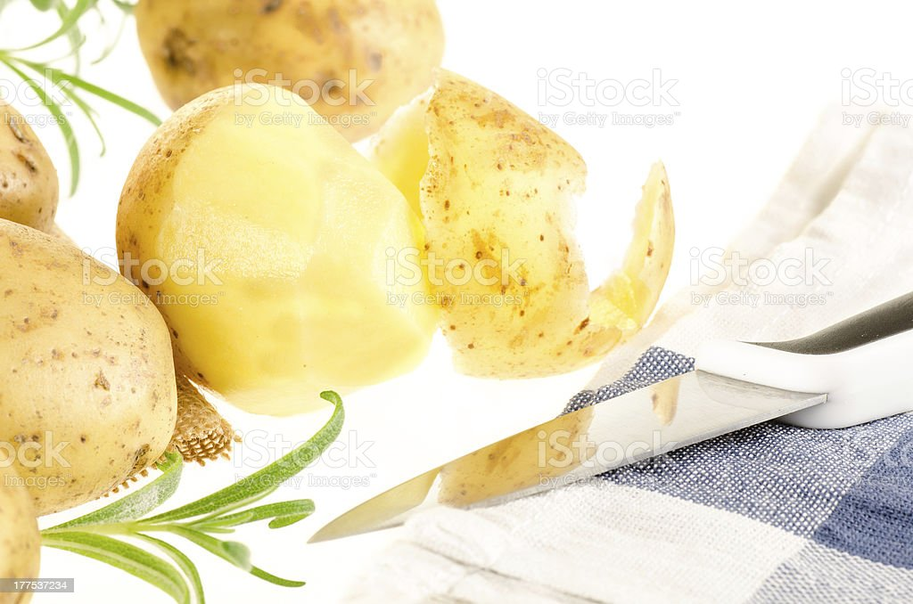 Fresh ripe potatoes and rosemary with knife, kitchen towel royalty-free stock photo