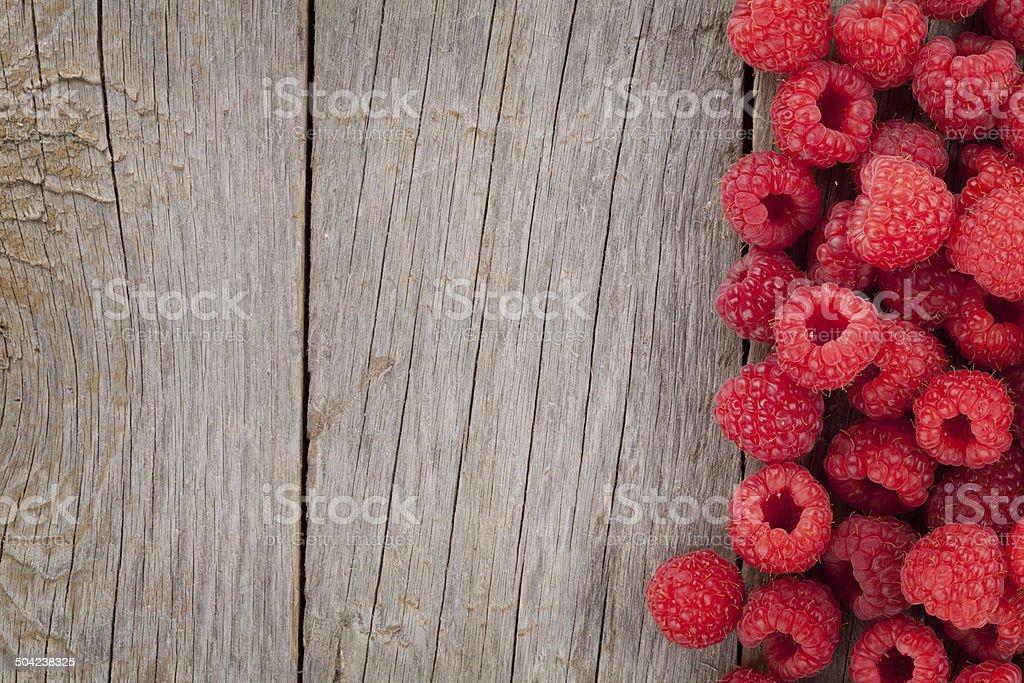 Fresh ripe raspberries on wooden table stock photo