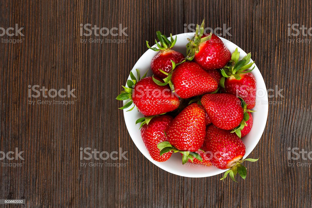 Fresh ripe strawberries in a simple white bowl stock photo