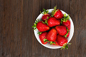 Fresh ripe strawberries in a simple white bowl