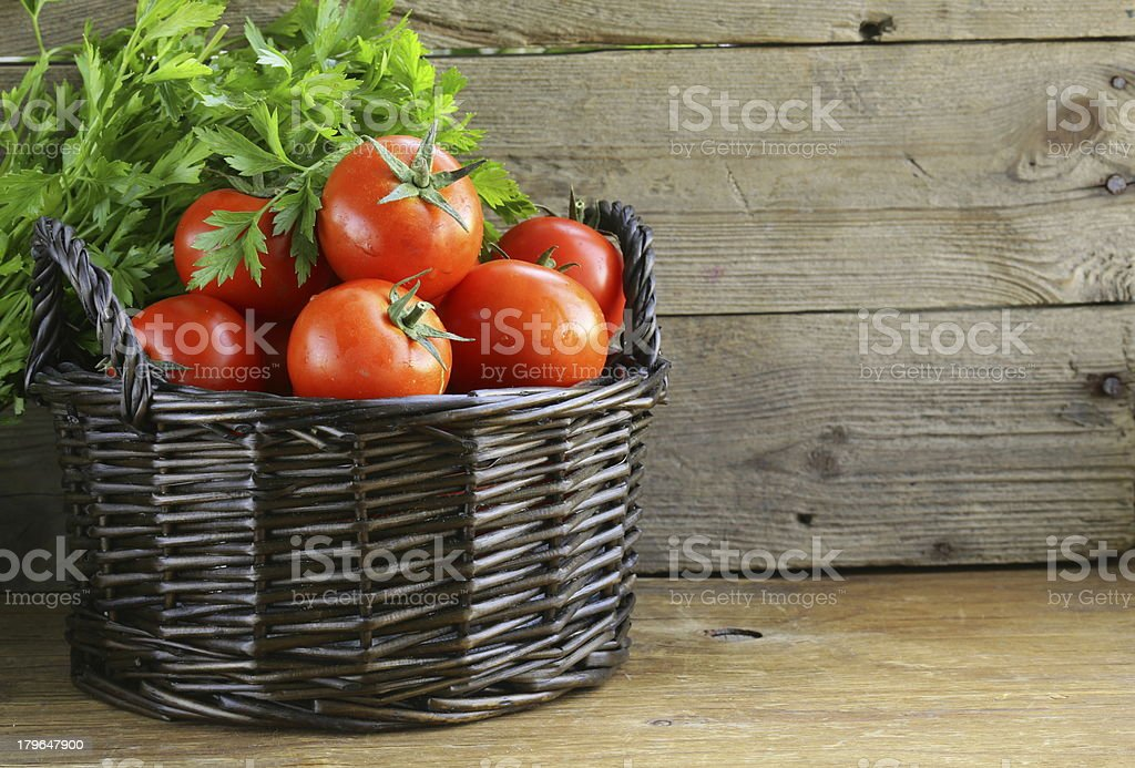 fresh ripe tomatoes in a basket on the table royalty-free stock photo