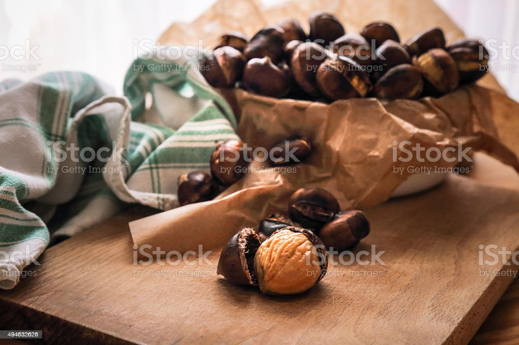 Fresh roasted chestnuts on wooden cutting board stock photo