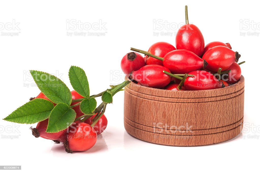 fresh rosehip berries in a wooden bowl isolated on white stock photo