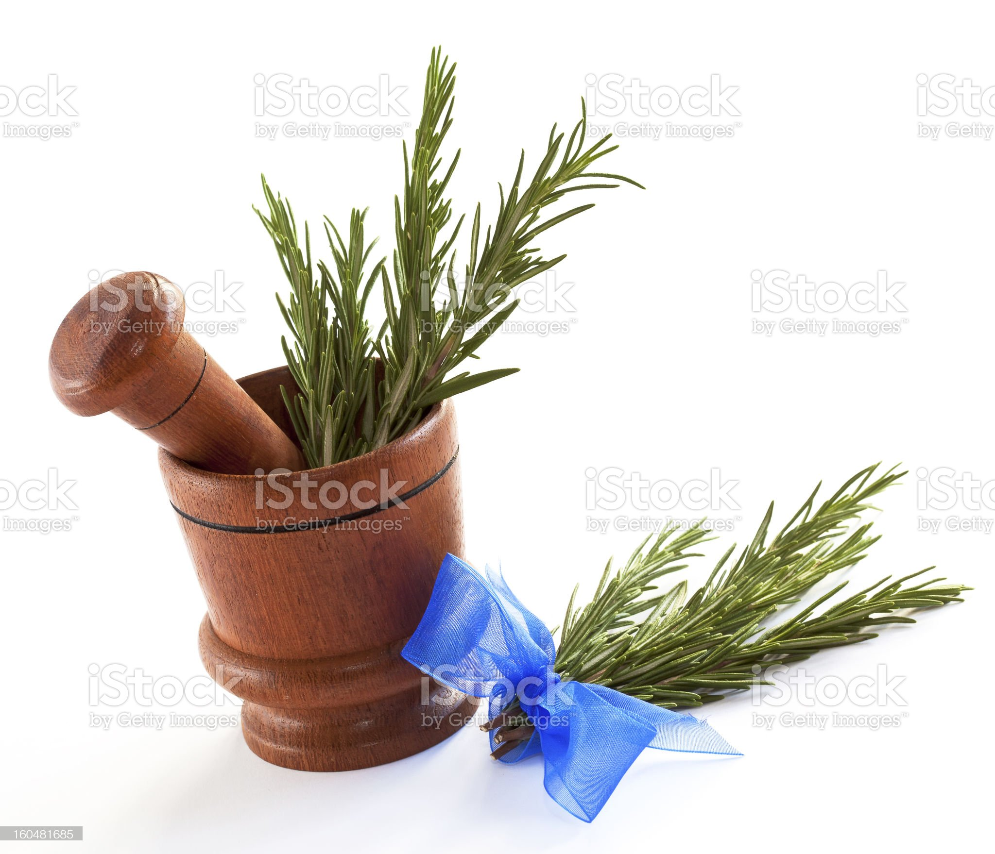 Fresh rosemary herb in wooden mortar with pestle royalty-free stock photo