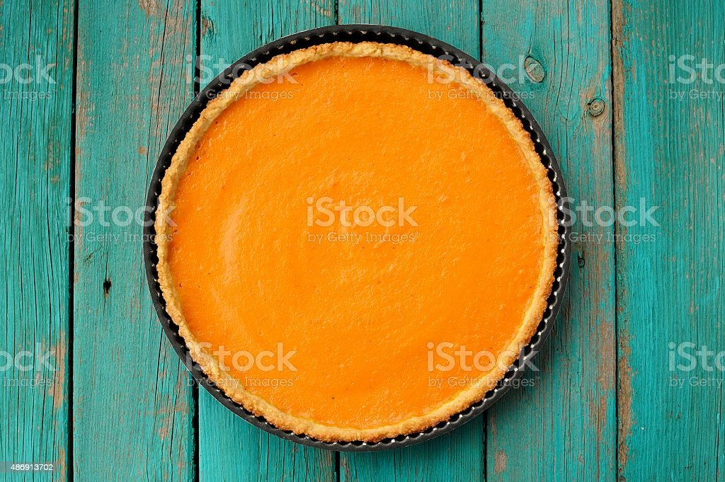 Fresh round bright orange homemade pumpkin pie in baking dish stock photo