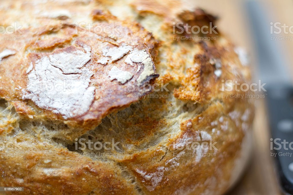 Fresh Round Loaf of Bread, Bread Knife, Cutting Board stock photo