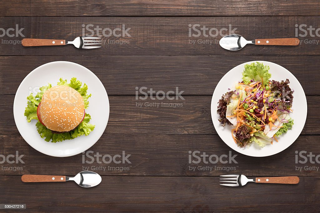 Fresh salad and burger on the wooden background. contrasting foo stock photo