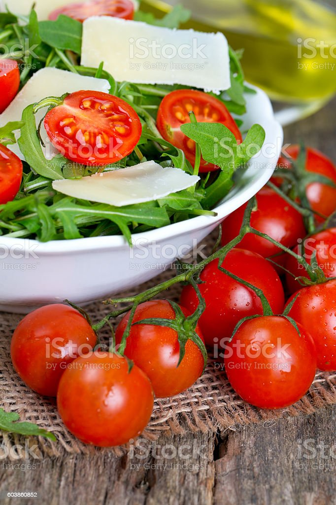 fresh salad from rucola, cherry tomatoes and parmesan cheese stock photo