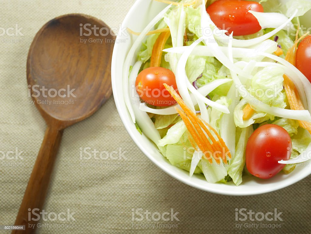 Fresh salad in bowl and wooden spoon stock photo