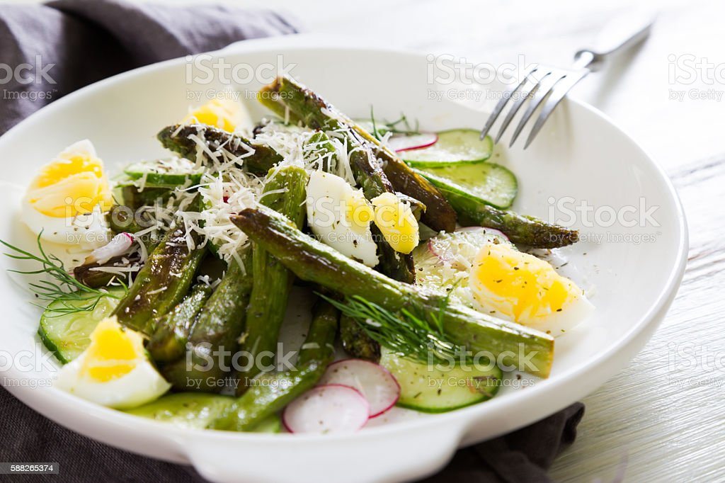 Fresh salad of asparagus, cucumber and boiled eggs with parmesan stock photo