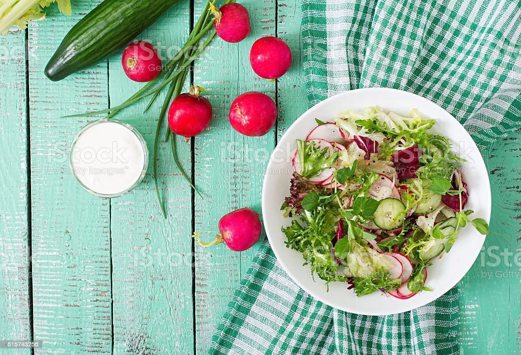 Fresh salad of cucumbers, radishes and herbs. Top view stock photo