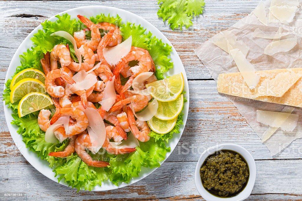 fresh salad of shrimps, green lettuce and slice of lemon stock photo