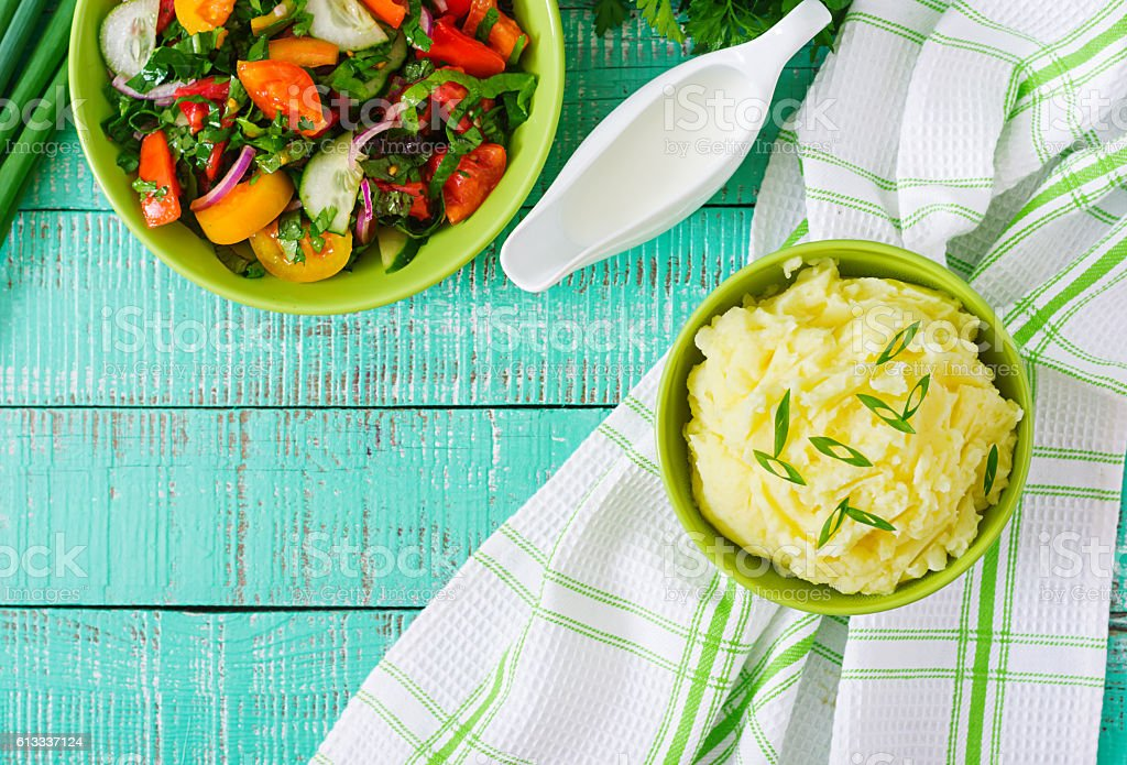 Fresh salad of tomatoes, cucumbers and bowl of mashed potatoes. stock photo