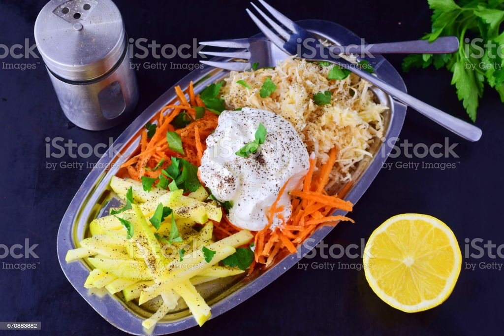 Fresh salad with celery, apple, carrot with yogurt on a metal plate on a grey background. Healthy eating concept. Dieting stock photo