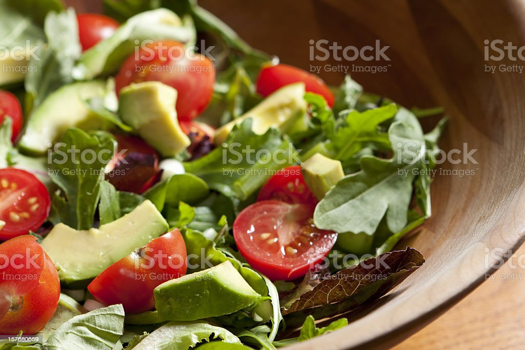 Fresh salad with cherry tomatoes, avocado and mixed greens stock photo