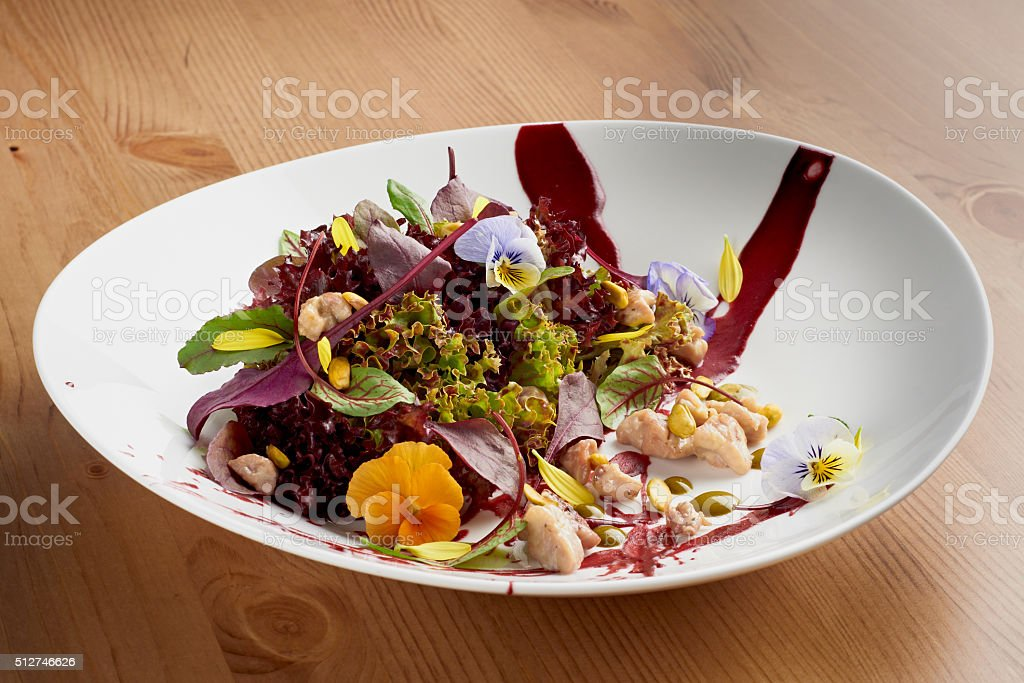 Fresh salad with chicken, lettuce and edible pansies stock photo