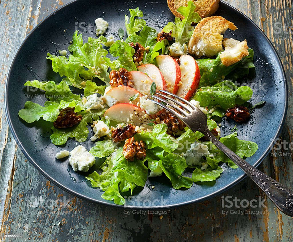 Fresh salad with pear, blue cheese and caramelized walnuts stock photo