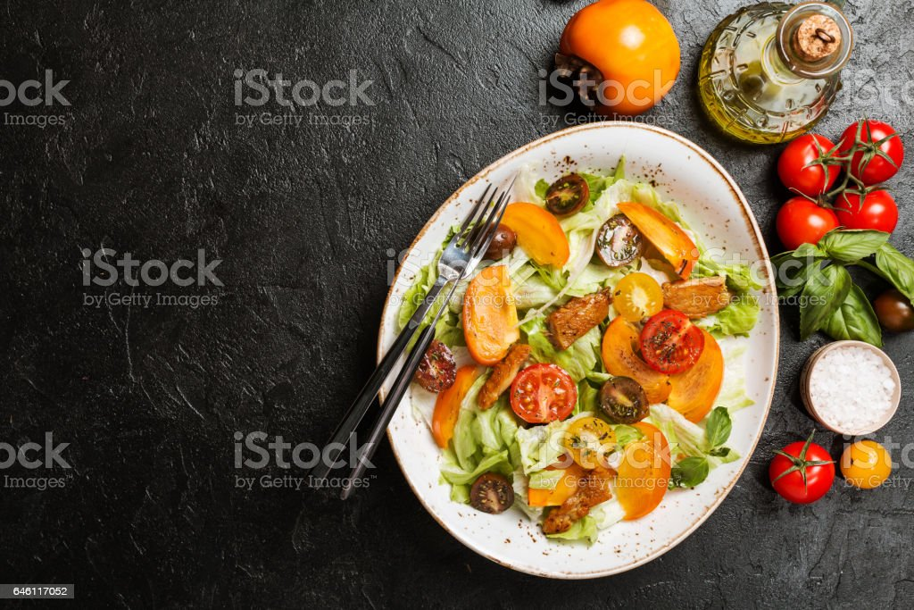 Fresh salad with persimmon stock photo