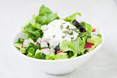 Fresh salad with thyme in a white bowl