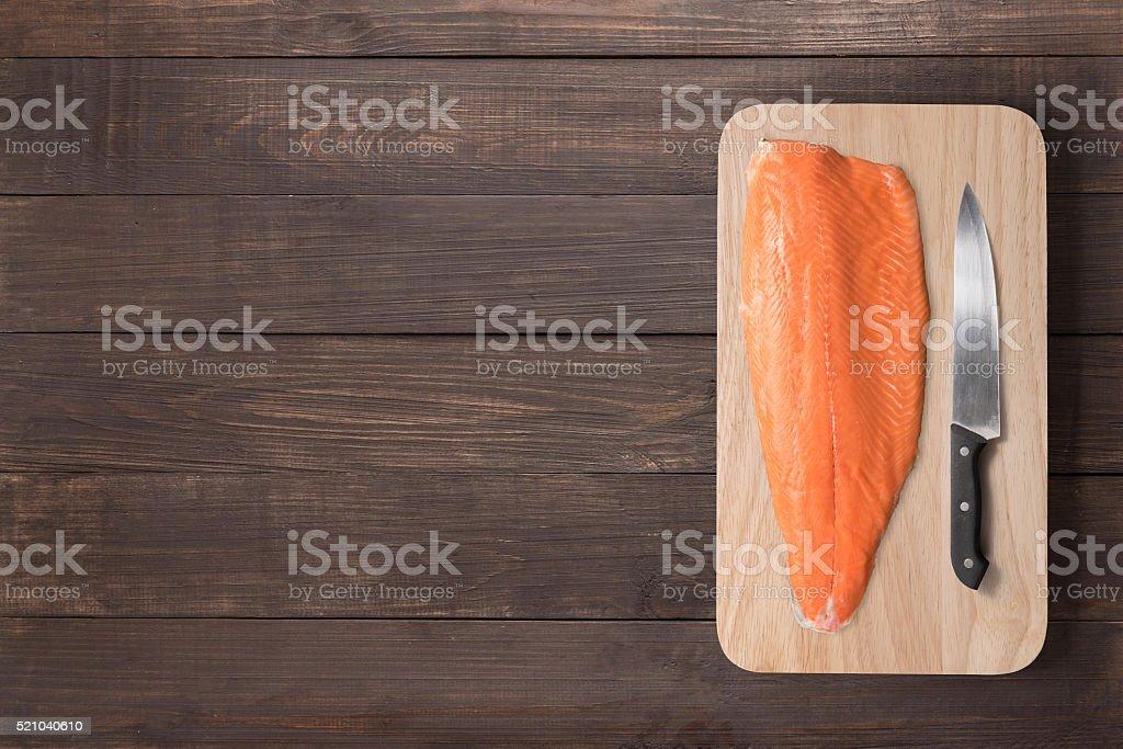 Fresh salmon and knife on cutting board stock photo