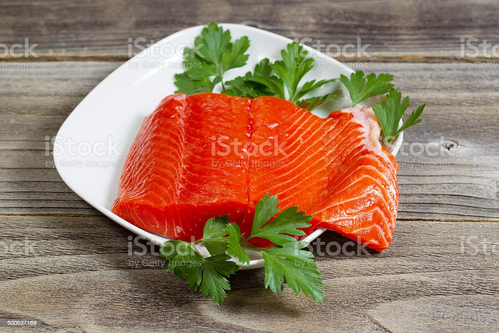 Fresh Salmon Fillet in white dish on rustic wood stock photo