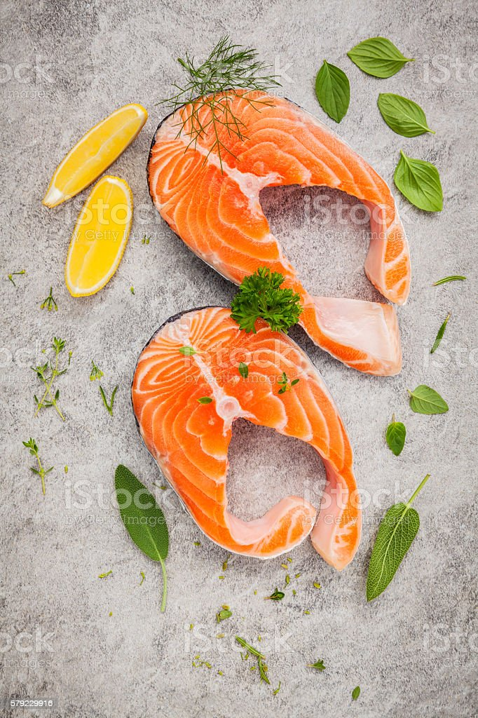 Fresh salmon fillet slice on dark stone background . stock photo