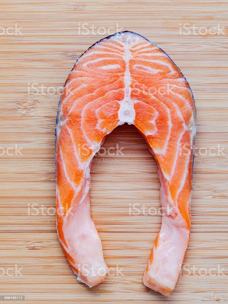 Fresh salmon fillet sliced flat lay on bamboo cutting board. stock photo