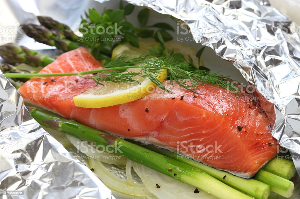 fresh salmon with asparagus in foil paper, ready for cooking stock photo