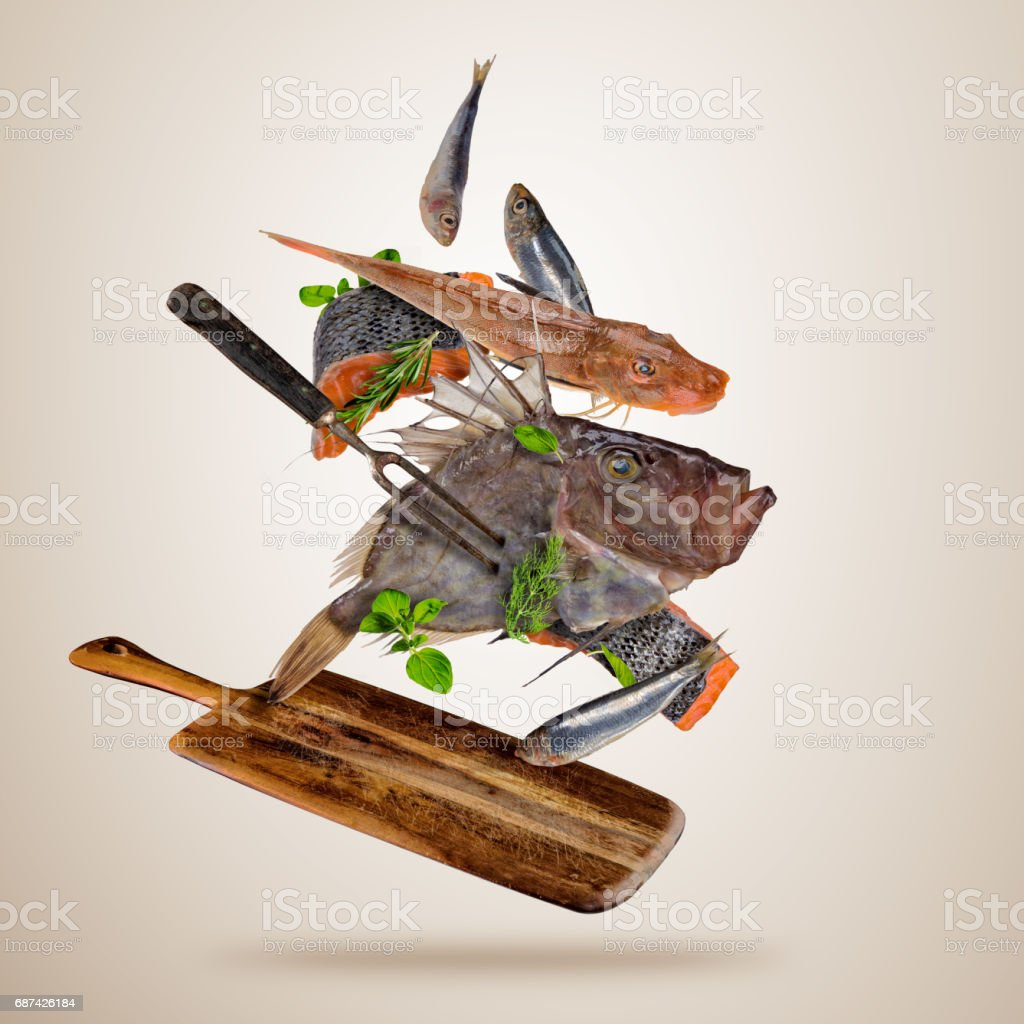 Fresh sea fish with falling spices, flying above wooden board stock photo
