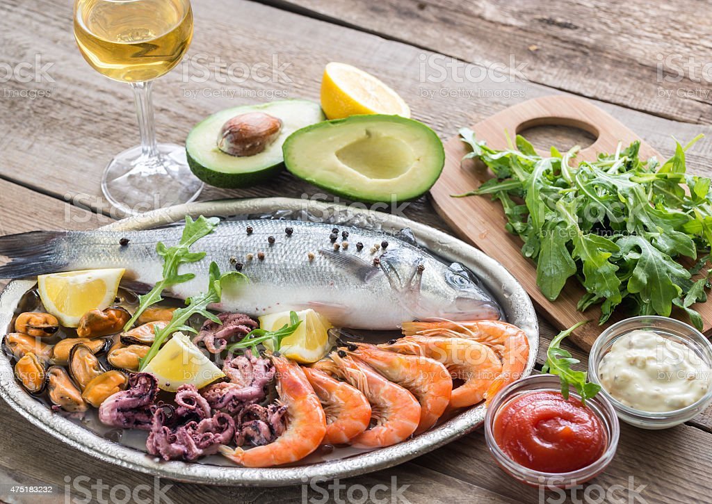 Fresh seabass with seafood on the tray stock photo
