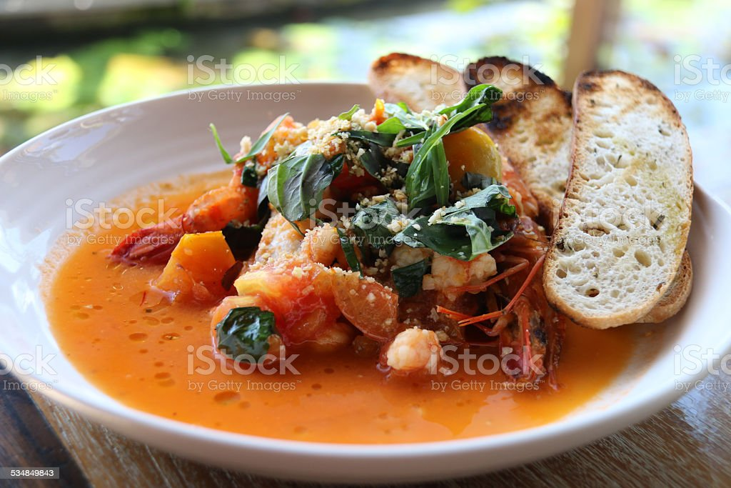 Fresh seafood and tomato-saffron soup with crostini stock photo