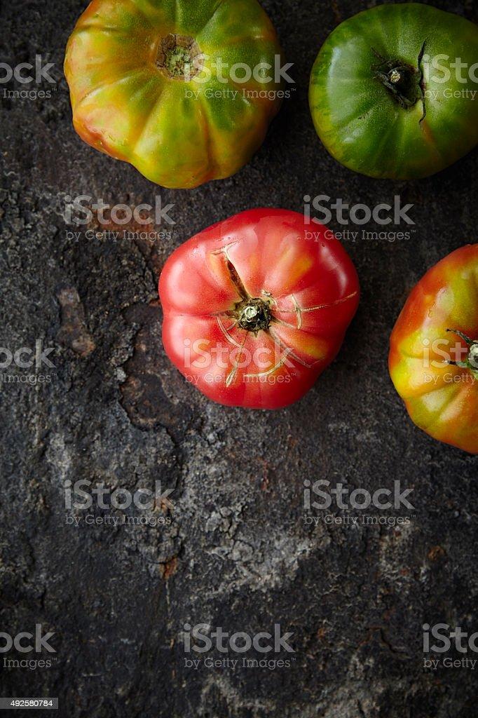 Fresh seasonal tomatoes on dark rusty surface stock photo