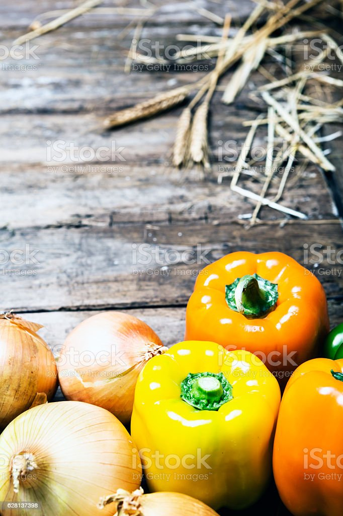 Fresh shiny yellow vegetables on weathered wood with copy space stock photo