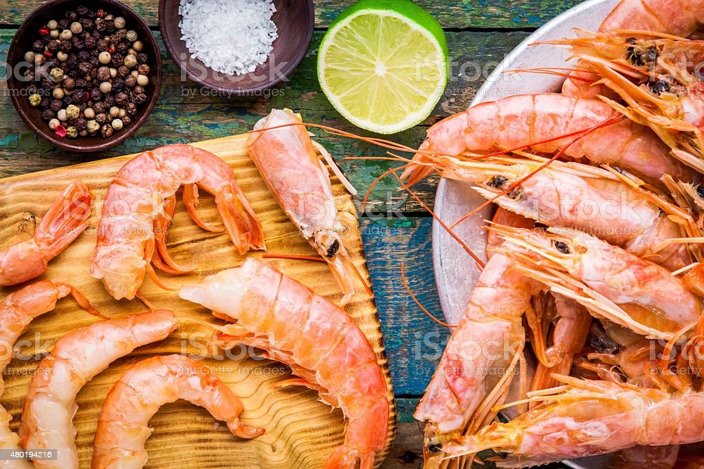 fresh shrimps on wooden board with salt, pepper, lime closeup stock photo
