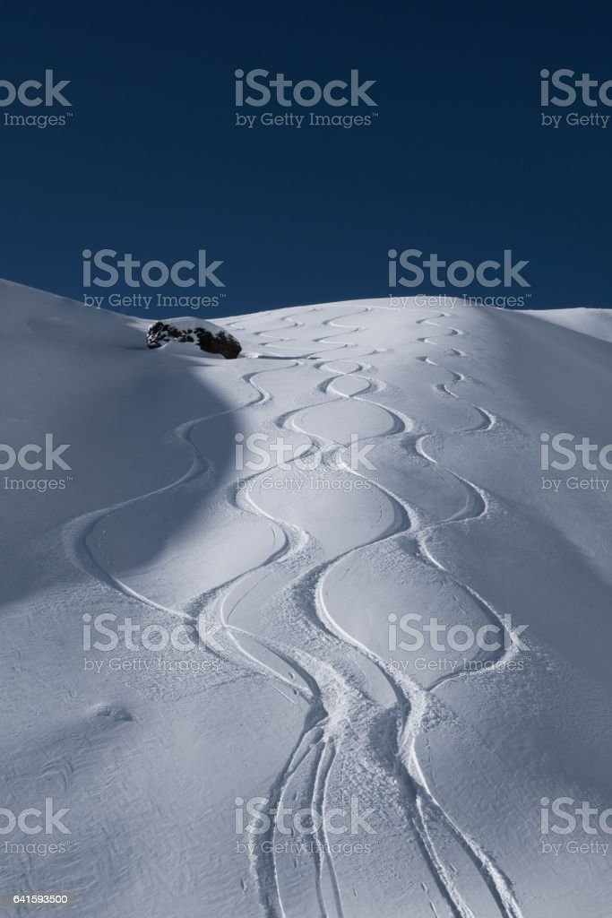 Fresh ski tracks leading down from alpine mountain ridge stock photo