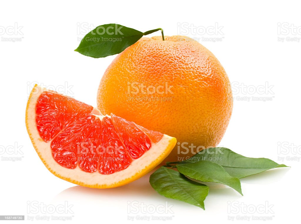 A fresh slice of grapefruit and a whole grapefruit isolated stock photo