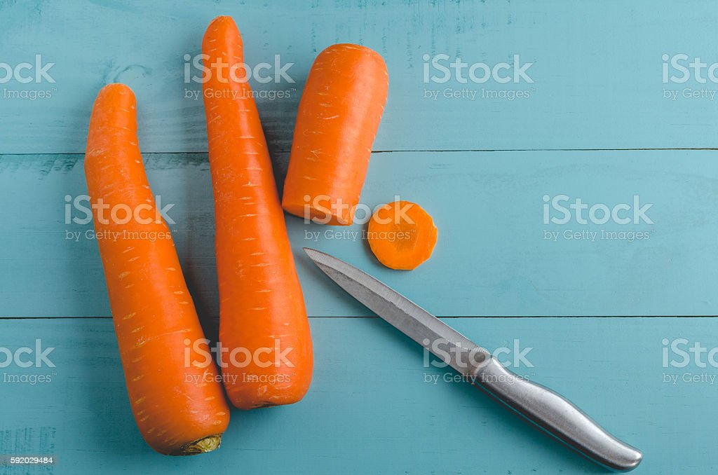 Fresh sliced carrots with knife on blue wooden board stock photo