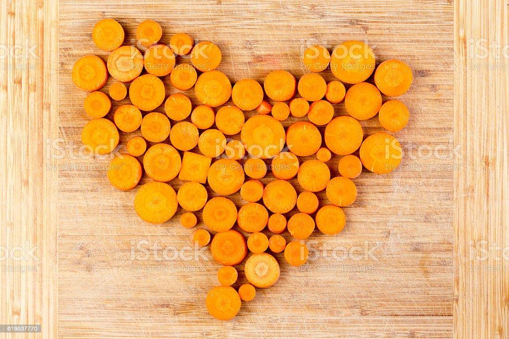 Fresh sliced orange carrots arranged in a heart stock photo