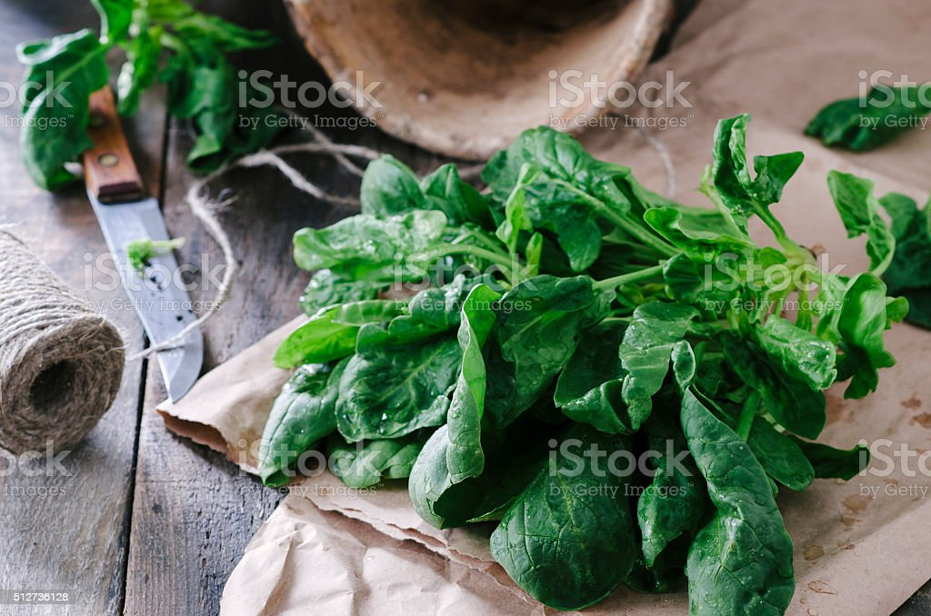 Fresh spinach in a old ceramic pot on wooden table stock photo